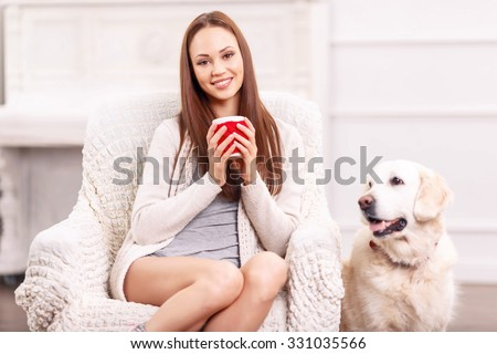 Buoyant time of the day. Adorable young girl with cute cup of tea and her pet near her is smiling genuinely. - stock photo