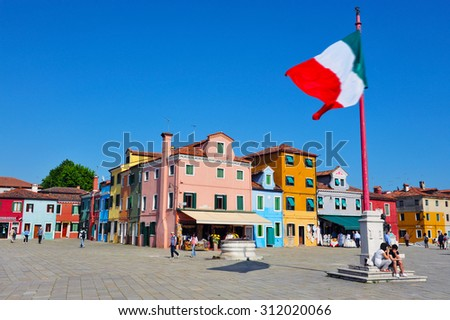 BURANO ISLAND, ITALY - MAY 01 2011:the national flag of Italy fly above Burano island main piazza square. Burano Island is known for its small, colorful brightly painted houses, popular with artists. - stock photo