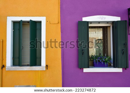 Burano island, Venice. Decorated window with bouquet of flowers. Colorful houses island and landmark of Veneto region, Italy