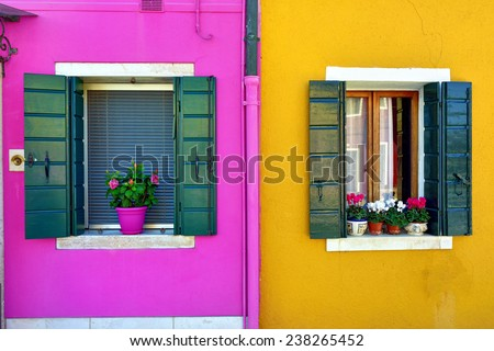 Burano island, Venice. Decorated window with bouquet of flowers. Colorful houses island and landmark of Veneto region, Italy - stock photo