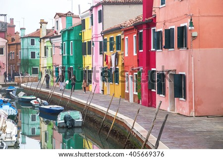 Burano, Italy - December  22, 2015: Scenic view  Burano island in Venetian lagoon. Tourists walking and taking photo of  canal, colored houses and boats. Venice. Italy. Travel, architecture concept.
