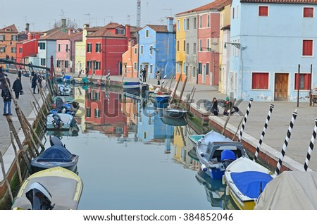 BURANO, ITALY - JANUARY 27: Tourists enjoying the colorful houses along the canal on the beautiful island of Burano: January 27, 2016 in Burano, Italy - stock photo