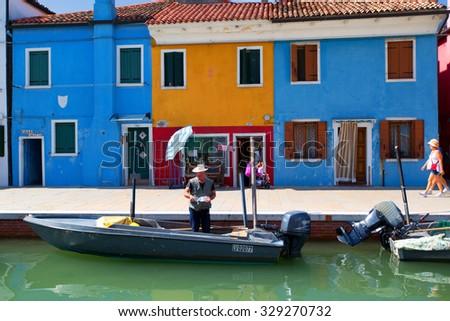 BURANO, ITALY - SEPTEMBER 17, 2015: Venice landmark, Burano island canal, colorful houses and boats, Italy.  - stock photo