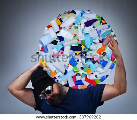 Burden of pollution - man carrying a globe made of plastic bottles, environmental destruction concept - stock photo