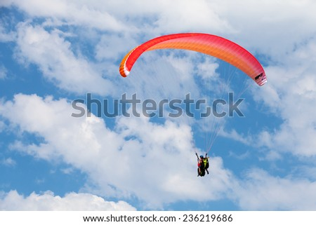 Burgas, Bulgaria - July 23, 2014: Red paraglider in the blue sky with clouds
