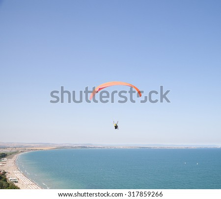 Burgas - July 25: Aerial photos - tandem paragliding flight with orange against the blue sky on July 25, 2015, Burgas, Bulgaria