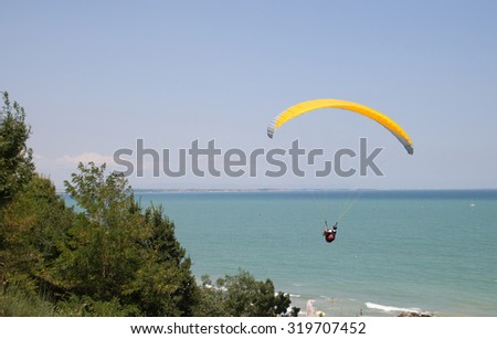 Burgas - July 24: Competition Accuracy landing paragliding - yellow paraglider flying against the blue sky and sea, July 24 to 26, 2015 to July 24, 2015, Burgas, Bulgaria
