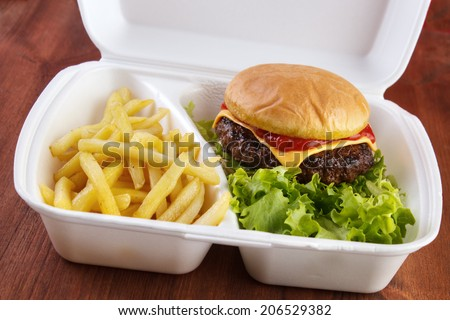 Burger and fries portion in takeout food box - stock photo
