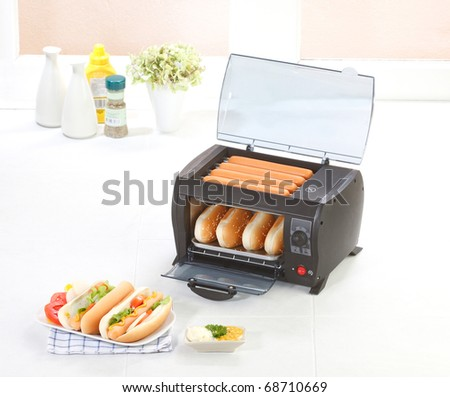 Burger and sausages grill machine in the kitchen - stock photo