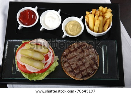 Burger, french fries and sauces from top view - stock photo