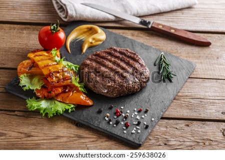 burger grill with vegetables and sauce on a wooden surface - stock photo