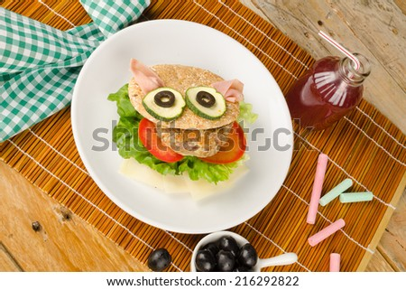 Burger in whole wheat bun decorated as a face, kid food