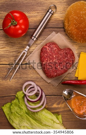 Burger ingredients over rustic wooden table. Top view - stock photo