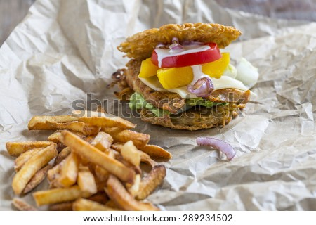 Burger made of asian Ramen noodles with chicken mango tomato cheese red onions and avocado creme and fries  - stock photo