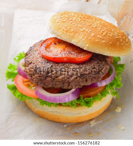 Burger made with pure ground beef. Garnished with red onions, tomatoes and lettuce on a hamburger bun, topped with sesame seeds.  - stock photo