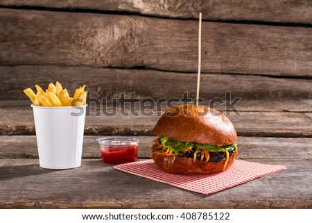 Burger on stick with fries. Fresh hamburger on wooden table. Juicy lettuce and hearty meat. Best dish in local bistro. - stock photo