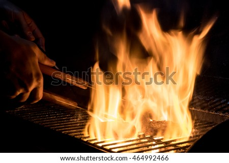 Burger patty cooking with a flame in the on the cooking grate