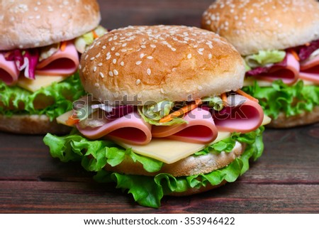 Burger sandwich with sausage, cheese and vegetables on a wooden background - stock photo