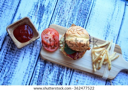 burger tomato cheddar cheese french fries red onion ketchup in wooden bowl on a cutting board on a wooden background/hamburger fries ketchup/horizontal burger and fries - stock photo