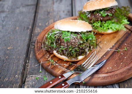 Burger with a young green salad on a wooden board - stock photo