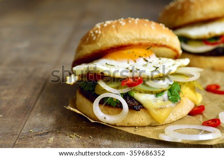 Burger with beef liver cutlet and fried egg on rustic background. - stock photo