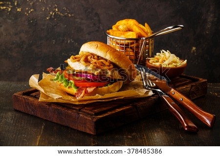 Burger with chicken breast and fried onions with coleslaw and potato wedges on dark background - stock photo