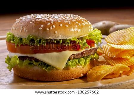 Burger with chips on wooden plates,and black background. - stock photo