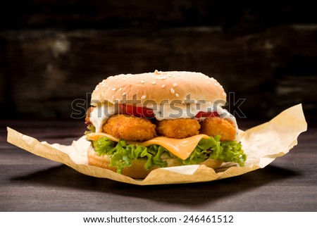 Burger with fish fingers fresh lettuce, tomato and tartar sauce - stock photo