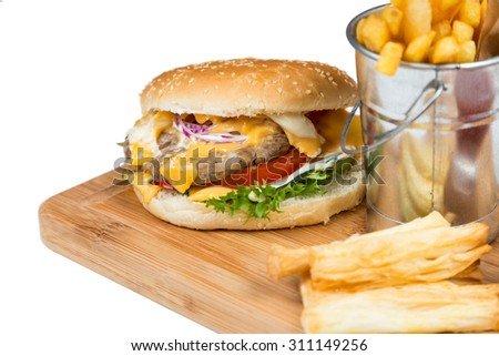burger with fried potatos in bucket serving on wooden board - stock photo