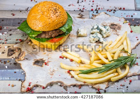 burger with fries on parchment paper.gourmet hamburger on colorful rustic table - stock photo