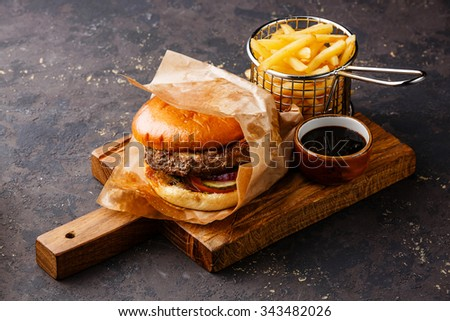 Burger with meat and French fries in serving basket on dark background - stock photo