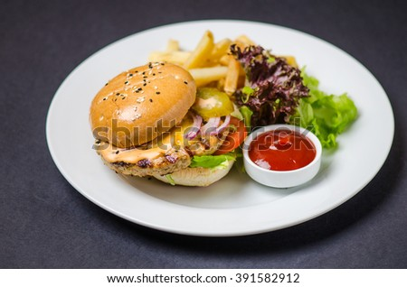Burger with meat patty , cheese , onions, tomatoes , pickled cucumbers , green salad , potato chips and sauce . Close-up in white plate on a black background.