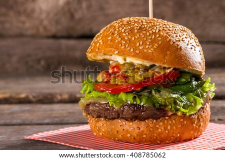 Burger with tomatoes on stick. Freshly cooked hamburger on table. Juicy beef and fresh tomatoes. All the needed ingredients. - stock photo