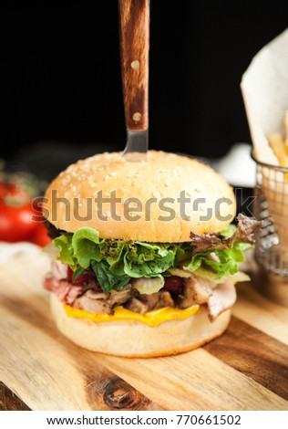 Burger with wheat loaf, French fries and salad on a wooden board