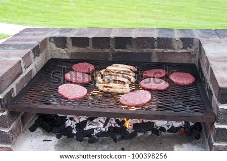 Burgers and sausages cooking on a brick barbecue
