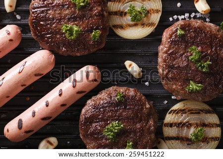 burgers and sausages with grilled vegetables macro. horizontal view from above