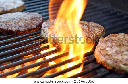 Burgers Cooking Over Flames On The Grill - stock photo