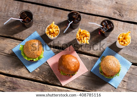 Burgers with fries and cola. Hamburgers with cola on table. Cool drinks and tasty burgers. Fresh vacation meal in diner. - stock photo