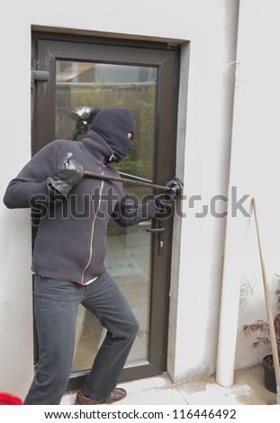 Burglar breaking door from outside with crow bar - stock photo