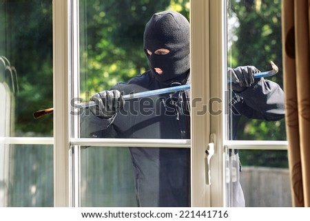Burglar breaking into a house via a window with a crowbar - stock photo
