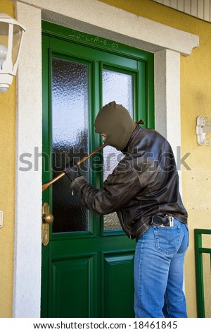 Burglar breaks into a residential building. - stock photo