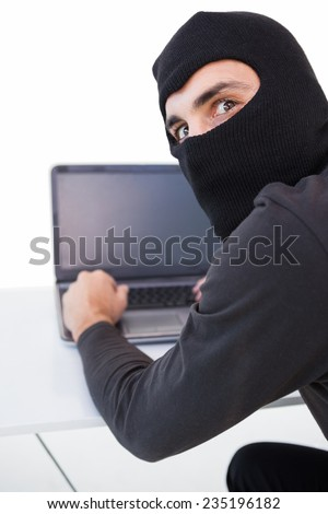 Burglar hacking into laptop while looking at camera on white background