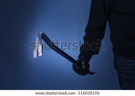 Burglar holding a crowbar in his hand. - stock photo