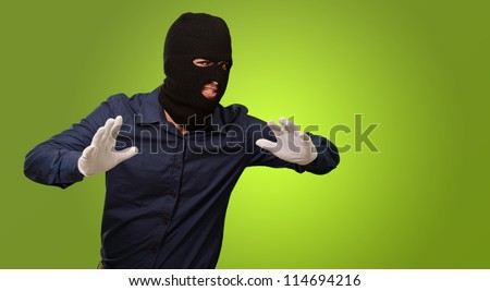 Burglar In Face Mask Isolated On Green Background - stock photo
