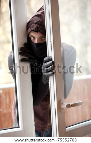 burglar  in mask and hood breaking into a house through window - stock photo