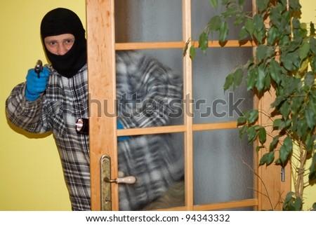 burglar in mask breaking into a house through door, with gun - stock photo