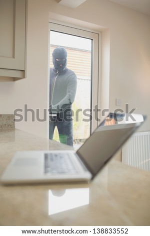 Burglar looking at laptop through the window of kitchen - stock photo