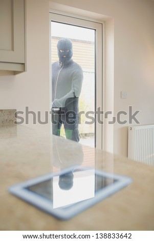 Burglar looking at tablet pc on kitchen counter through kitchen door - stock photo
