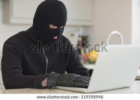 Burglar sitting in the kitchen and hacking a laptop - stock photo