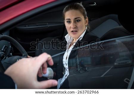 Burglar threatens young businesswoman sitting in car - stock photo